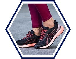 Closeup of black and pink women's running shoes with pink leggings.