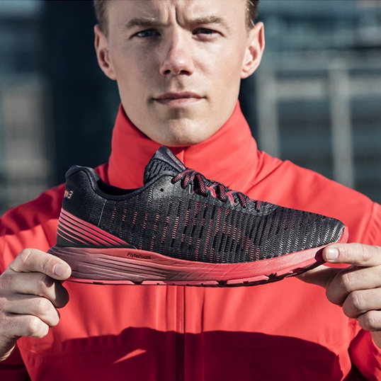 Man facing the camera and displaying a black and red running shoe.