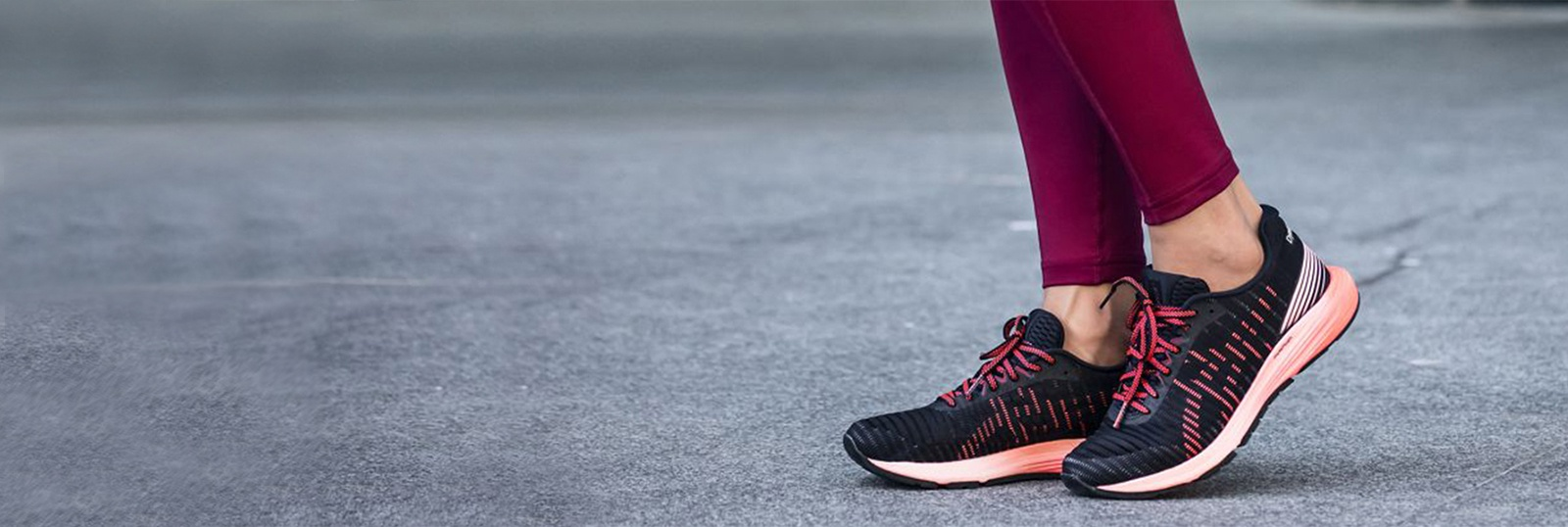 Closeup of women's legs and feet wearing black and pink running shoes and pink leggings.