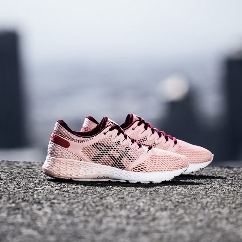 Women's pink running shoes sitting on pavement.