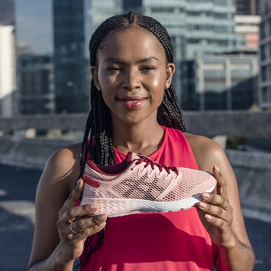 Woman in a pink tank top holding a light pink running shoe.