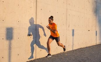 man in orange shirt running on gravel next to a cement wall
