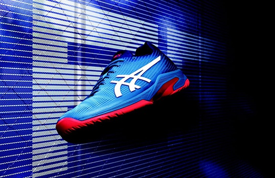 A blue and red tennis shoe flies through a dark blue background.