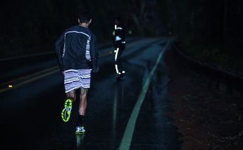 lite-show. two males running at night in rain