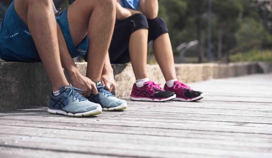 male & female sitting - focus on shoes; male is tying shoes