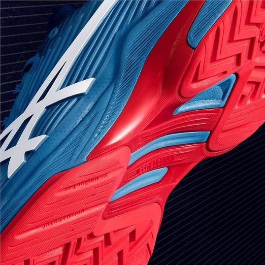 Closeup of the outsole of a red and blue tennis shoe.
