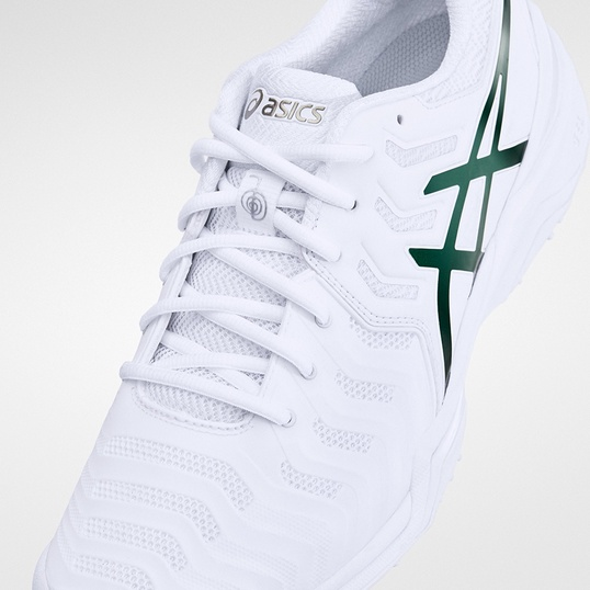 A white tennis shoe with green accents.