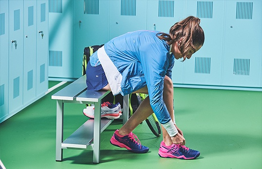 A woman dressed in a tennis skirt ties her shoes in a green locker room.