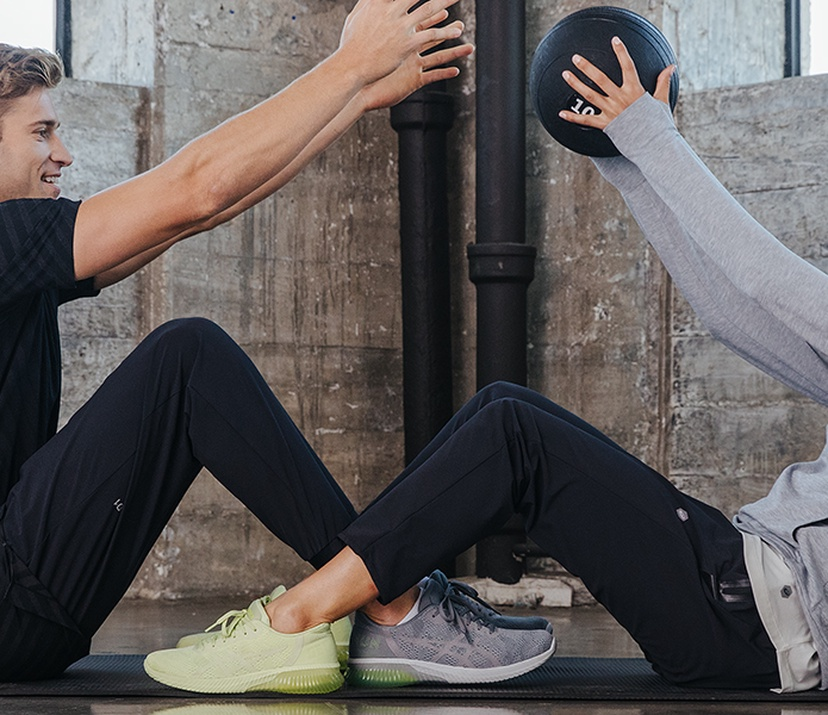 Two people passing a medicine ball between them