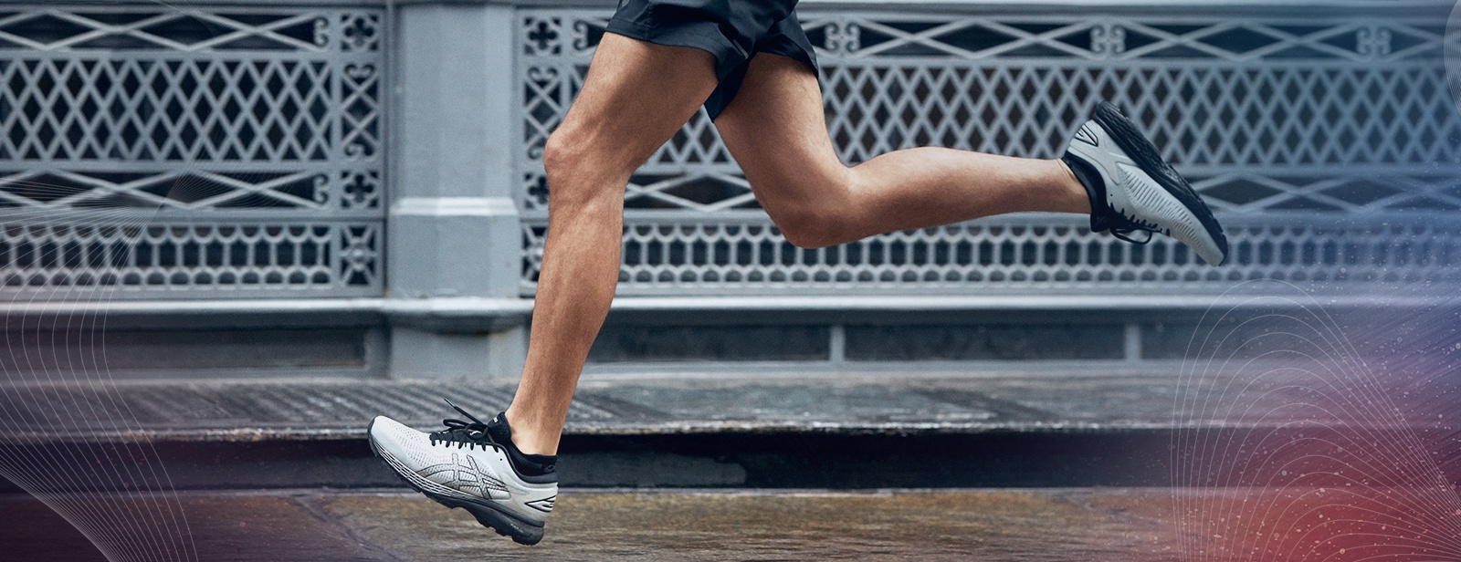 Closeup of the legs of a man running in shorts and white shoes.