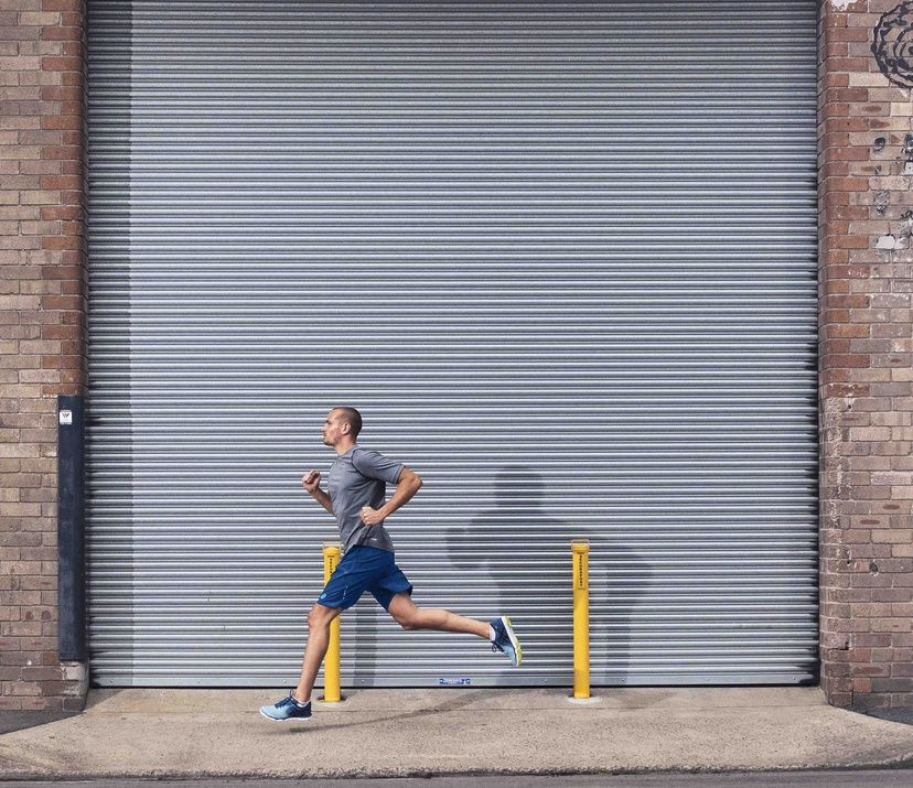 man running on streets; warehouse metal slidding door behind him