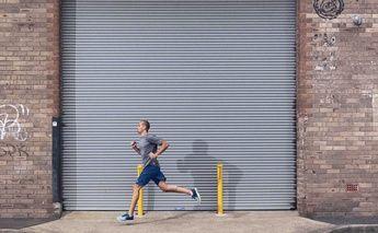 man running on streets; warehouse metal slidding door behind him