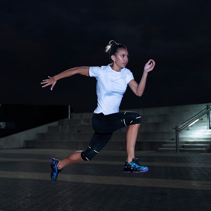 A Women running while wearing ASICS Lite-show shoes and apparel